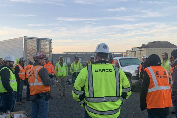 Crew members gathered in a circle for a safety meeting wearing Garco high visibility vests