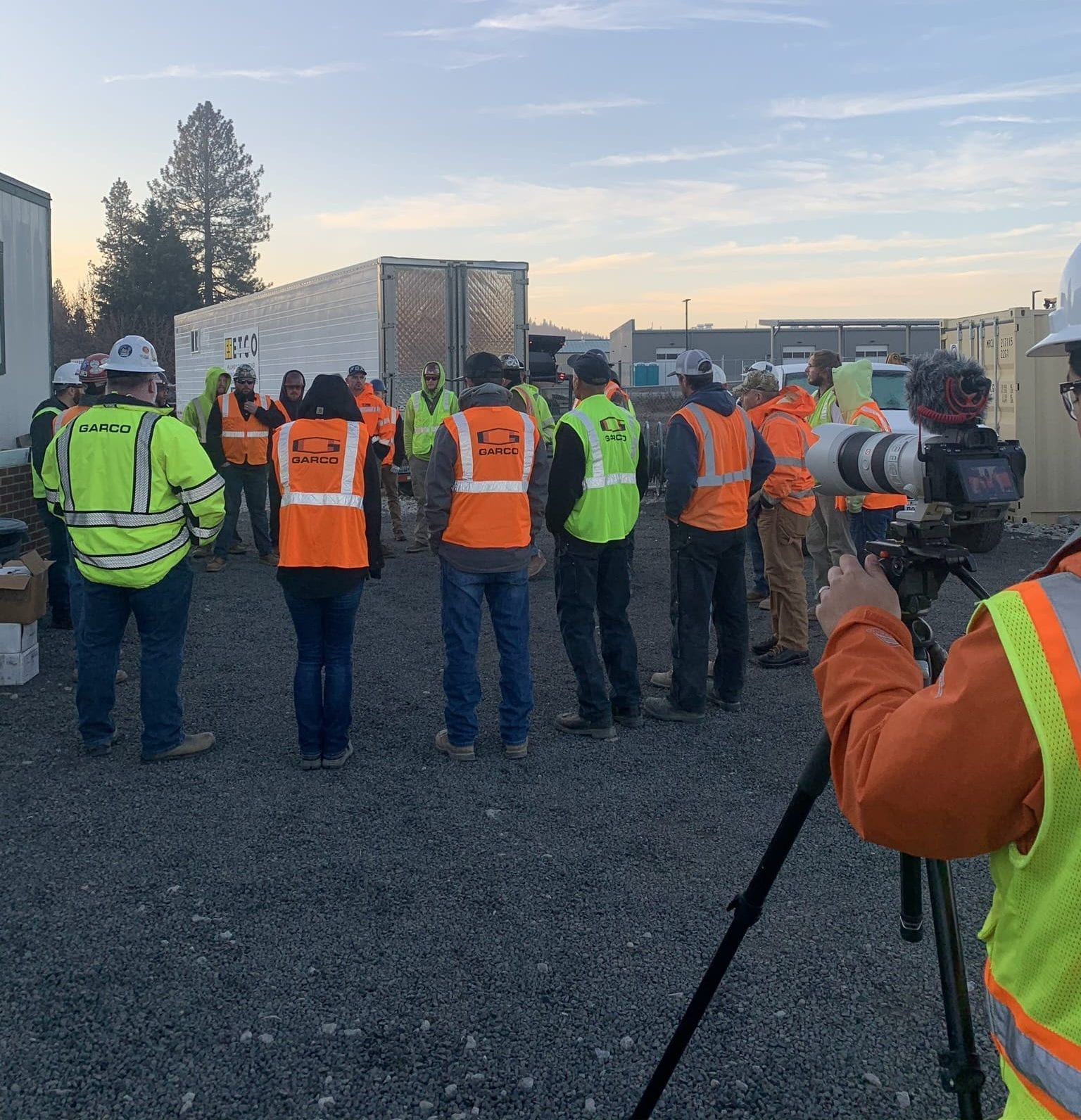 Production team filing the crew gathered in a circle wearing their high visibility safety vests