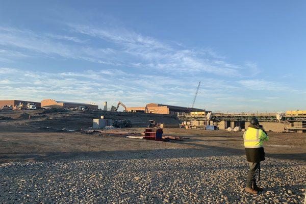 Camera man in high visibility jacket filming building demolition job site